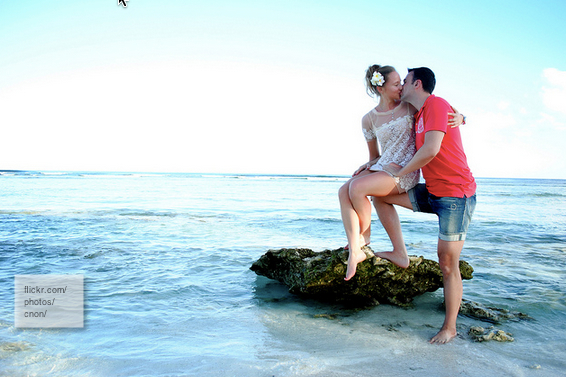 young couple kissing on ocean